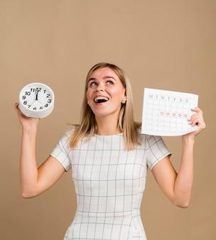 Klok en periode kalender gehouden door vrouw