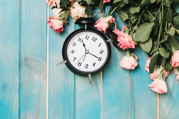 Klok en roze rozen