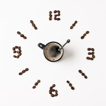 Klok gemaakt van koffiebonen en mok