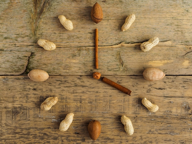 Klok gemaakt van verschillende noten en kaneel op houten tafel