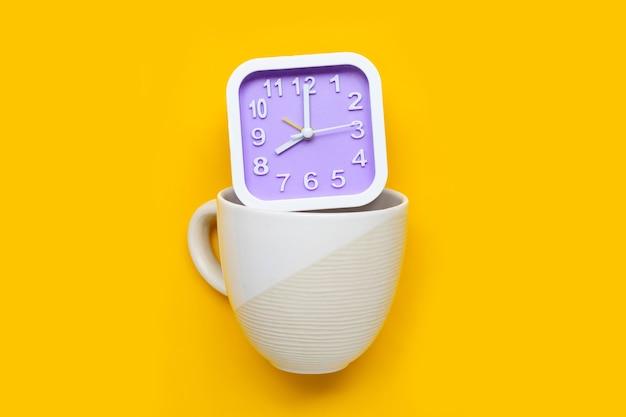 Klok in koffiekopje op gele achtergrond. ruimte kopiëren