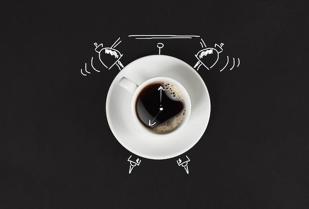 Klok kopje verse espresso met klok teken op zwarte achtergrond