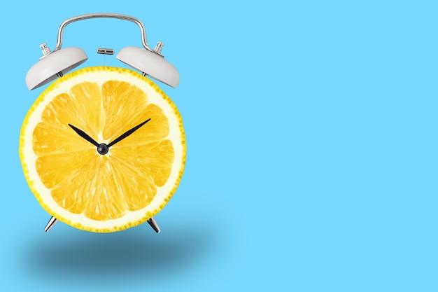 Klok met citroen wijzerplaat op blauw. creatief concept.