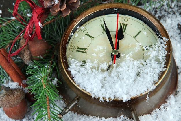 Klok met dennentakken en kerstversiering onder de sneeuw close-up