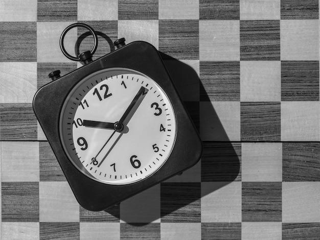 Klok met handen op de achtergrond van een zwart-wit schaakbord. plat leggen.