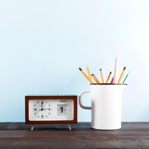 Klok met kalender in de buurt van mok met potloden
