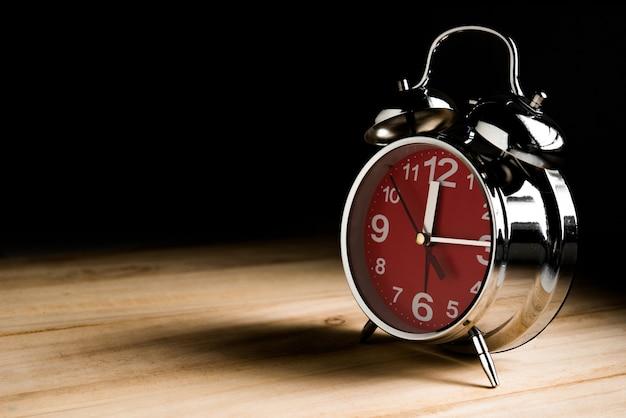 Klok om 12 uur op houten tafel in donkere toon met zwarte achtergrond