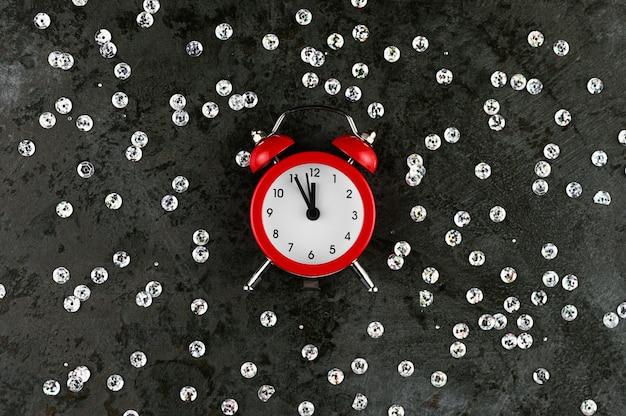Klok op een grijze achtergrond met glitters toont twaalf uur op oudejaarsavond