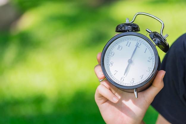 Klok op hand die tijd toont om 6 uur op groen park