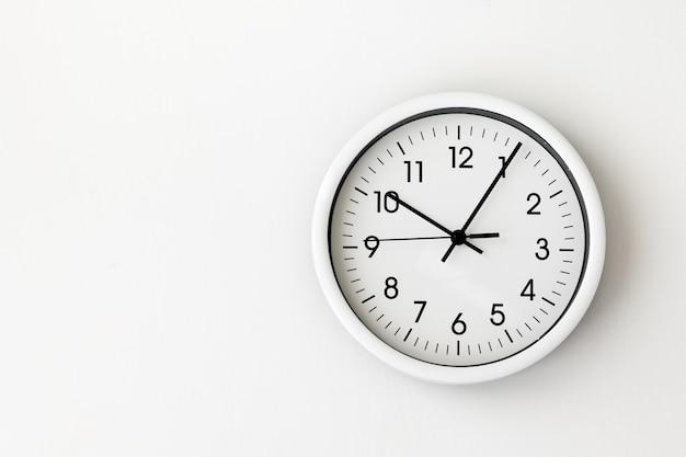 Klok, witte pijl klok op witte achtergrond vrouw hand met een ronde klok met zwarte pijlen, controle, timing, tijdbeheer, tijd, kom, laat, minuten verliezen, tweede