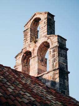 Klokkentoren en het rode pannendak van de kerk op de blauwe hemel. details van de oude stenen kerk in de oude stad, budva, montenegro. mediterrane architectuurstijl.