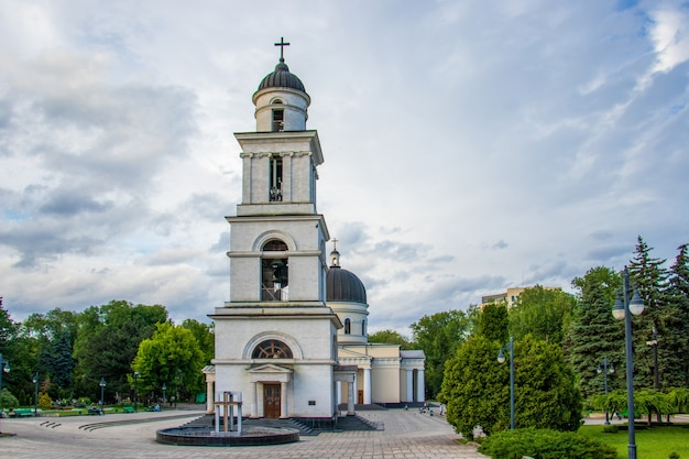 Klokkentoren van de kathedraal van de geboorte van christus, omringd door bomen in chisinau, moldavië