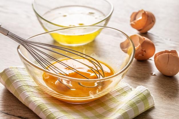 Klop de eidooiers in een glazen kom met eiwitten in een tweede kom en gekraakte eierschalen aan de zijkant.