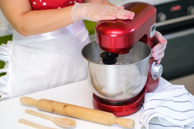 Klop de eiwitten tot schuim. opgeklopt eiwit voor een meringue. rode stationaire mixer, keukenmachine