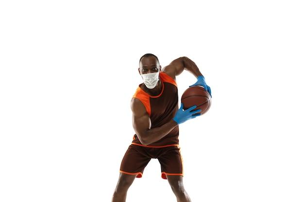 Klop het af. afro-amerikaanse basketbalspeler met beschermend masker. nog steeds actief tijdens quarantaine. gezondheidszorg, geneeskunde, sportconcept.