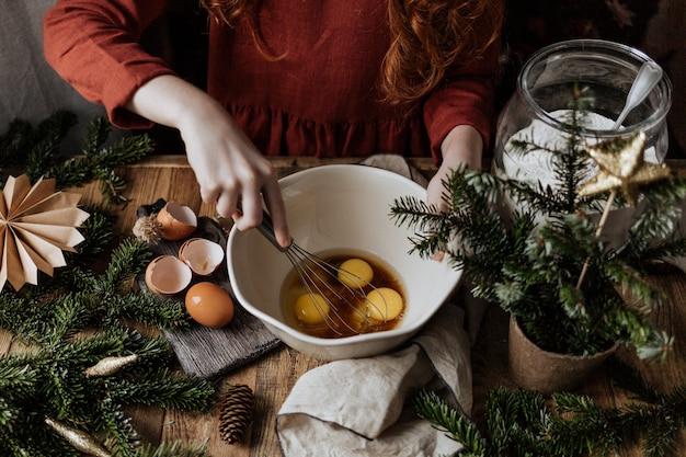 Klop op een houten tafel in een witte kom eieren met suiker.