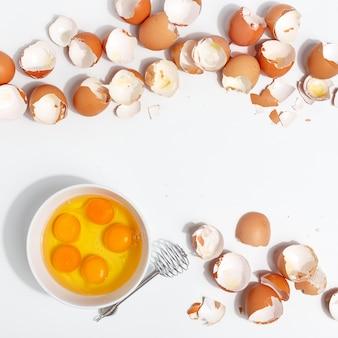 Kloppen eieren met garde. dooiers en ei-eiwitten in een kopje. corolla klop eieren. bereiding van voedsel en kippeneieren. eierschaal op een tafel. uitzicht van boven. Premium Foto