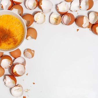 Kloppen eieren met garde. dooiers en ei-eiwitten in een kopje. corolla klop eieren. bereiding van voedsel en kippeneieren. eierschaal op een tafel. uitzicht van boven.