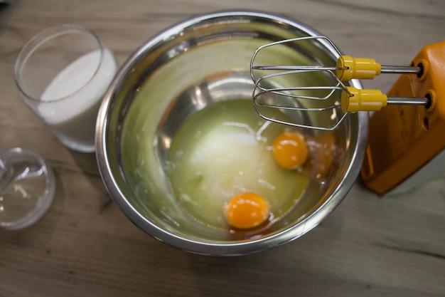 Klopt van elektrische mixer voor suiker en eieren in een kom