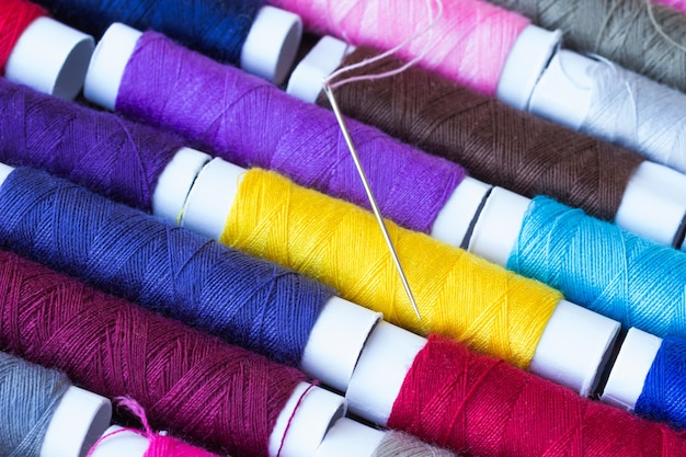 Klossen met gekleurd garen, naald en draad.