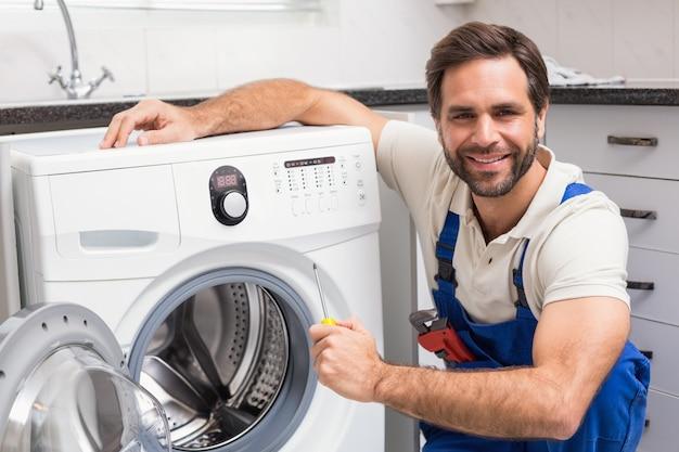 Klusjesman die een wasmachine bevestigt