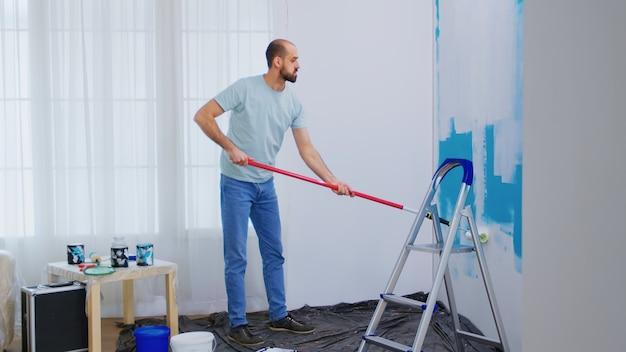 Klusjesman die huis renoveren. muur schilderen met rolborstel gedrenkt in witte verf. klusjesman aan het renoveren. appartement herinrichting en woningbouw tijdens renovatie en verbetering. repareren en decoreren