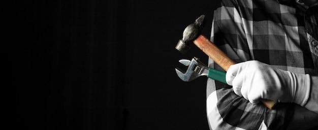 Klusjesman hand in handschoenen close-up met hamer en moersleutel tools op zwarte achtergrond met kopie ruimte.