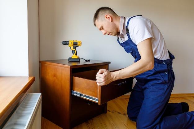 Klusjesman in blauw uniform werkt met automatische schroevendraaier elektriciteit. huis renovatie conceptie.