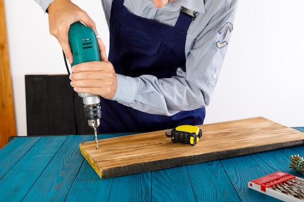 Klusjesman in blauw uniform werkt met elektrische automatische schroevendraaier. huis renovatie concept.