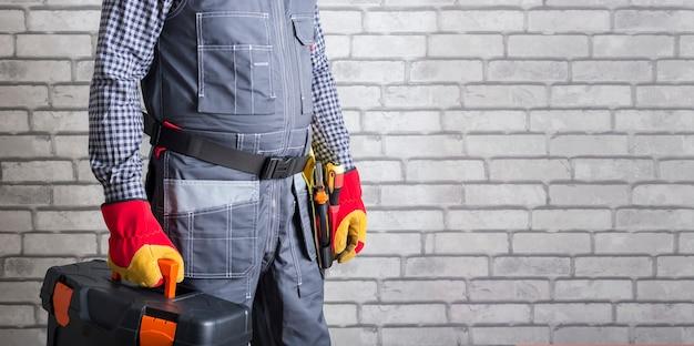 Klusjesman met gereedschapskist en gereedschapsriem tegen bakstenen muuroppervlak met kopieerruimte. banier. reparatie service.