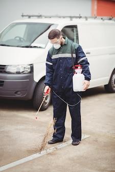 Klusjesman met insecticide staat voor zijn busje
