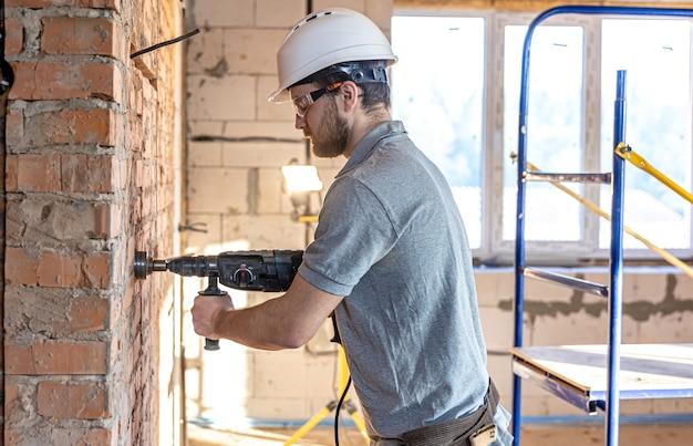 Klusjesman op een bouwplaats tijdens het boren van een muur met een perforator