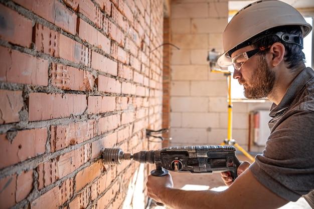 Klusjesman op een bouwplaats tijdens het boren van een muur met een perforator.