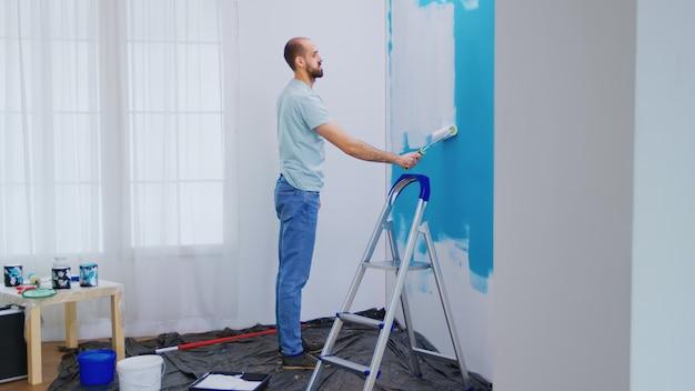 Klusjesman schilderij muur met rolborstel gedoopt in witte verf. klusjesman aan het renoveren. appartement herinrichting en woningbouw tijdens renovatie en verbetering. reparatie en decoreren.