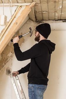 Klusjesman staande op een ladder en een huis renoveren, met behulp van hulpmiddelen zoals een hamer