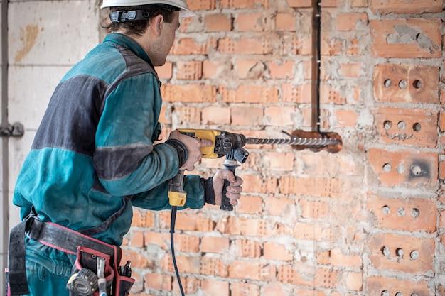 Klusjesman tijdens het boren van een muur met een perforator.