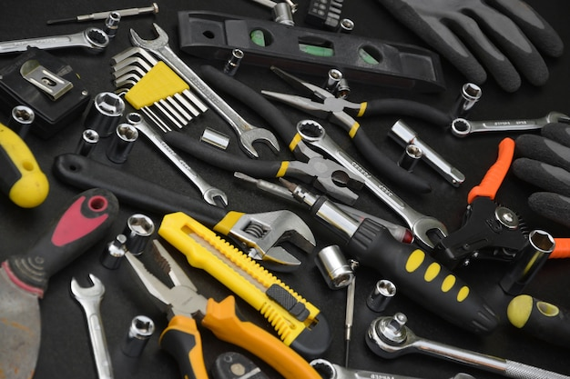 Klusjesman toolkit op zwarte houten tafel. veel sleutels en schroevendraaiers, pilers en ander gereedschap voor alle soorten reparatie- of constructiewerkzaamheden. reparateur tools set