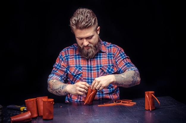 Klusjesman werken met leer met behulp van crafting tools in zijn atelier. leather worker maakt een nieuw leerwerk.
