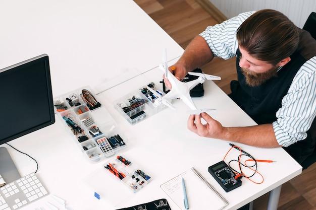 Klusjesman zoekt gebroken drone om reden van mislukking te vinden, bovenaanzicht. nieuw elektronisch apparaat, onbekende technologie, problemen op het werkconcept