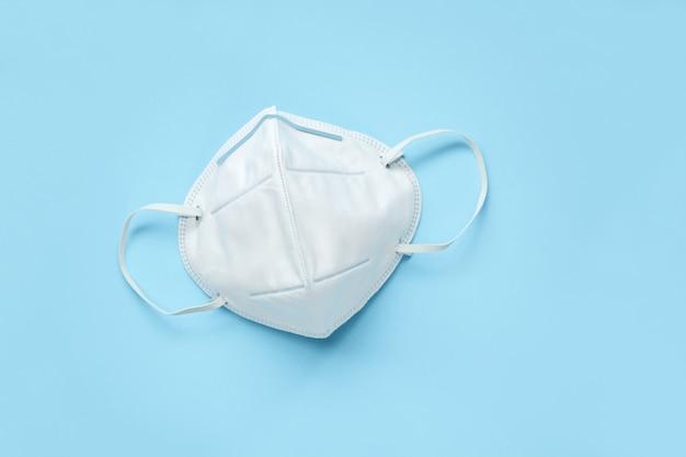 Kn95 gezichtsmasker op blauwe achtergrond bescherming tegen pm 2.5 vervuiling en covid-19 coronavirus. gezondheidszorg en medisch concept