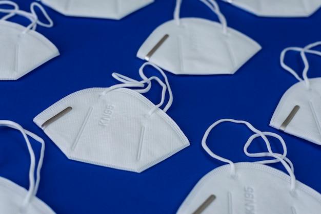 Kn95 of n95 wit masker met antiviraal medisch masker voor bescherming tegen coronavirus op blauw