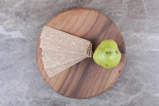 Knäckebröd en peer op het bord, op de marmeren achtergrond.