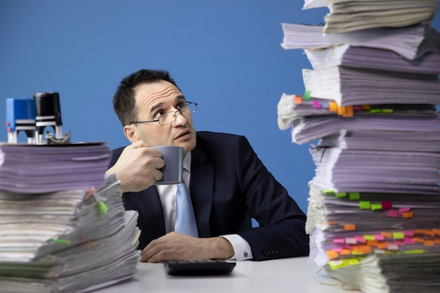Knackered kantoormedewerker kijkt bang naar hoge stapel documenten