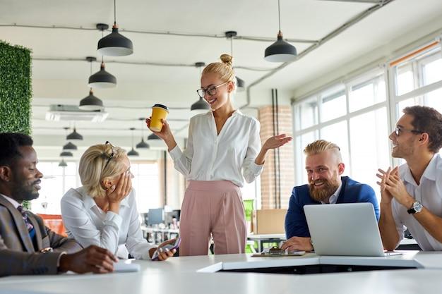 Knap, aangenaam, vrouwelijke baas, bespreekt zakelijke ideeën met werknemers