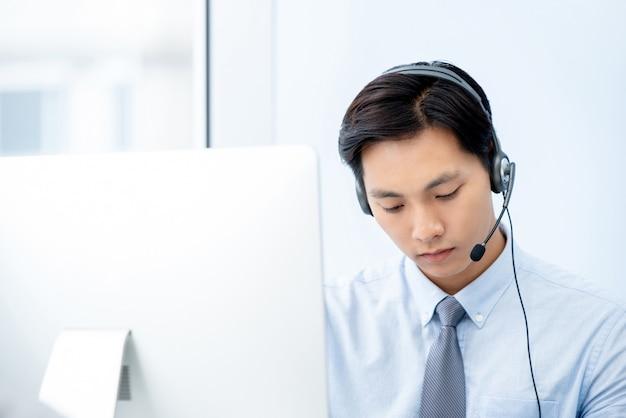 Knap aziatisch telemarketingpersoneel dat hoofdtelefoon draagt die zich bij het werken in bureau concentreert