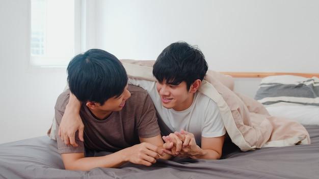 Knap aziatisch vrolijk paar dat op bed thuis spreekt. jonge aziatische lgbtq + man gelukkig ontspannen rust samen romantische tijd doorbrengen na wakker worden in slaapkamer in modern huis in de ochtend.