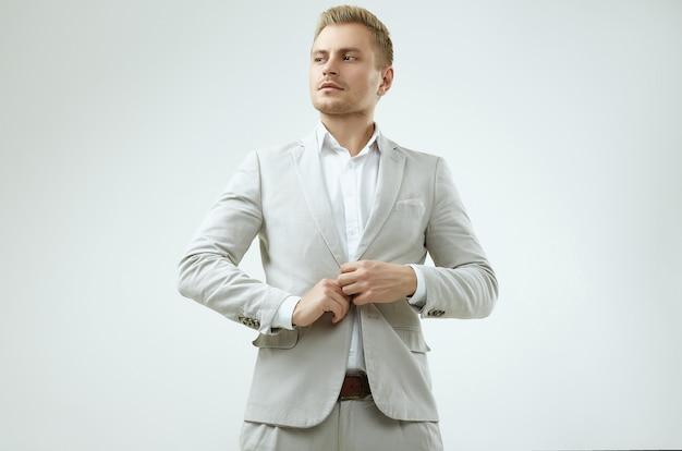 Knap blonde mensenmodel in een manier grijs kostuum in studio