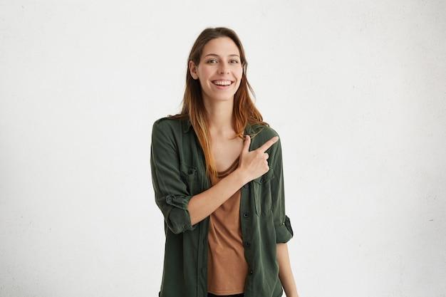 Knap en vrolijk jong wijfje dat vrijetijdskleding draagt die haar wijsvinger op witte lege muur met copyspace houdt