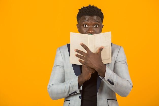 Knap jong afrikaans mannetje dat in een jasje een boek leest