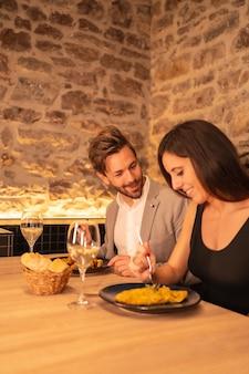 Knap jong koppel verliefd in een restaurant, met plezier samen eten, valentijnsdag vieren